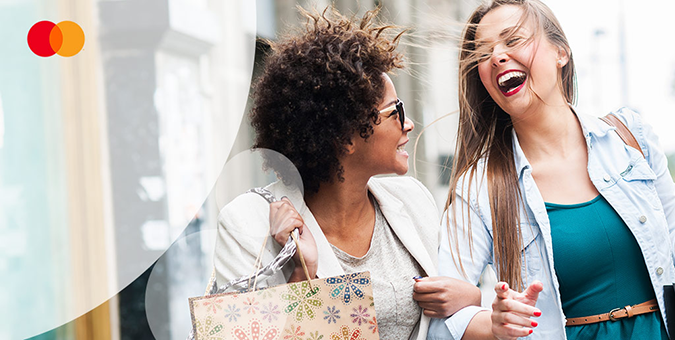 friends laughing while shopping using their SMB debit Mastercard®